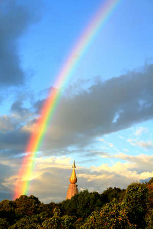 A rainbow that crosses the chedi and forest at Doi Inthanon National Park, Chiang Mai Province, Thailand. Land mark for tourist travel and visit in Northern of Thailand. Beauty in nature