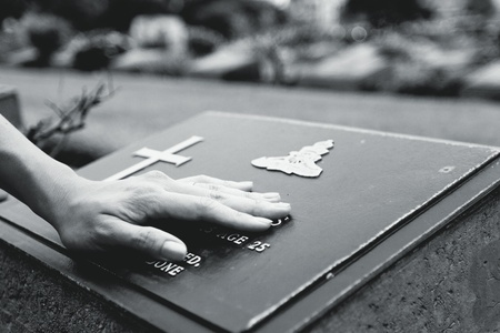 $Woman's hand touching the black stone grave. Reminisce, miss, sad and lose person in the family or important people concept in black and white style