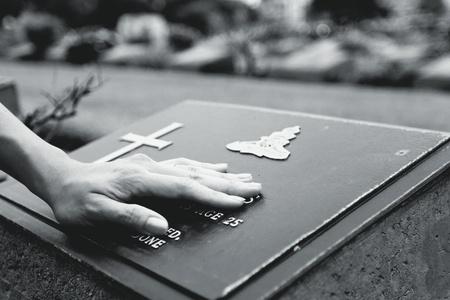 memorial cross: $ La mano de la mujer tocando la tumba de piedra negra. Recuerda, extravia, triste y pierde a la persona en el concepto de familia o personas importantes en estilo blanco y negro