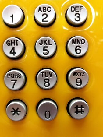 Gray or grey phone numbering keypad for press to call on yellow background.