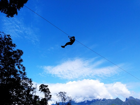 Silouette man or woman sling and flying on the sky with clouds, mountains and trees. Extreme and adventure sport concept.