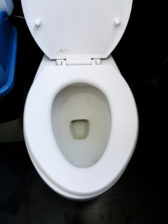 Close Up And Top View White Flushing Toilet, Water Closet Or Lavatory With  Black Floor