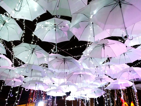Many white umbreallas hanging with light on night street. Art and Design concept