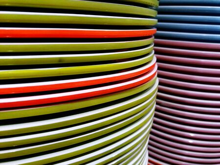 Close up many colorful ceramic dish or plate stacked in dishware store