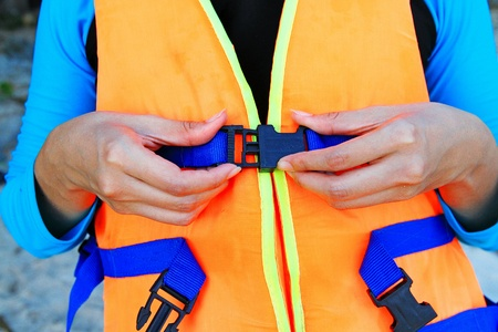 Woman or young girl wearing orange life vest or life jacket before going to swimming or scuba diving in the sea- Close up and focusedhands. Safety life and protect concept