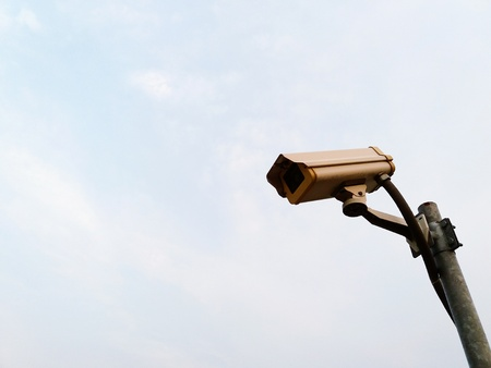 White surveillance camera or security cctv (Close Circuit Television) with installed on steel pole outdoor and monitor and record for property protection with white sky background and copy space.