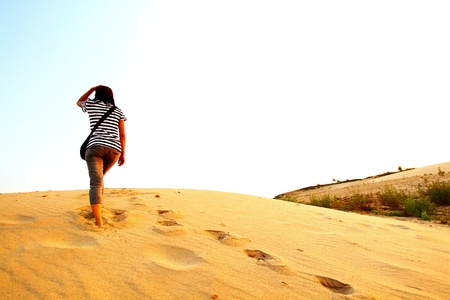 Asian woman lonely walking on small desert mountain  and many footprint on the sand with copy space at Sam Phan Bok, UbonRatchaThani, Thailand - People call grand canyon of Thailand and famous place