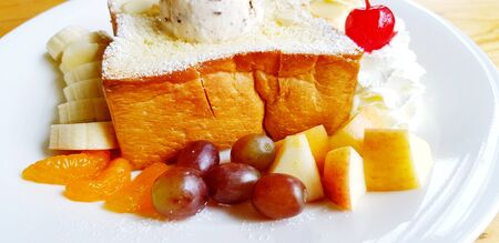 Close up honey toast with fresh fruit, whipped cream, vanilla ice cream on top bred in white plate or dish