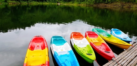 Many colorful canoeing or kayak boat parked on the rive for tourist and customers rent them with green tree plant background and copy space at Srinagarind Dam lake, Kanchanaburi Province, Thailand