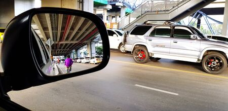 Bangkok- Thailand 13, 2018: Close up view side mirror of car seeing structure building, people and traffic jam with transportation and car moving for background - Transport and vehicle concept