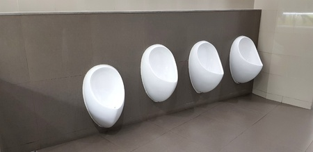 Four white urinal on the gray wall in men toilet or rest room - Object, Interior design and Sanitary ware concept Imagens