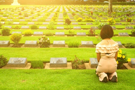 Kanchanaburi, Thailand - July 2, 2016: Asian woman sitting in front of black gravestone at graveyard with sunlight flare - Reminisce, miss, sad and lose person in family or important people concept