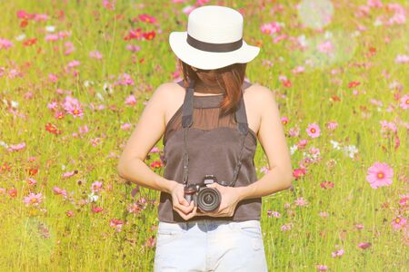 Chiangrai, Thailand - December 7, 2016: Hipster girl holding Nikon DSLR camera with orange sunlight flare and standing among in cosmos flowers garden for background Редакционное