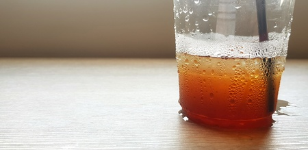 Close up plastic glass of water, iced coffee, coke or cola and straw putting on wooden table  with copy space - Refreshment, Cold, Thirsty, Drinking, Object, Background and water droplet  concept Banco de Imagens