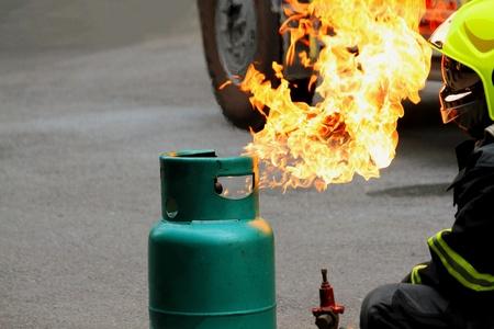 Il serbatoio del gas verde sta bruciando con il pompiere in uniforme che prepara il fuoco antincendio - concetto di carriera di salvataggio, protettivo e pericoloso