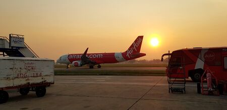 Bangkok, Thailand - January 21, 2019: Airplane taking off or landing on runway in the early morning with truck baggage to plane and Red bus transporting passenger to the plane at Don Muang airport