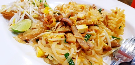 Close up Thai fried noodle or Pad thai with squid, octopus or cuttlefish, lime sliced, vegetable, tofu and stainless steel spoon on white plate - Famous Asian food in Thailand