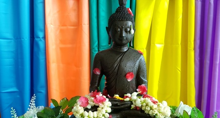 Black Buddha statue with petal red rose, Jasmine on colorful curtain background - Religion, Buddhist, Asia, Faithful and Respect concept