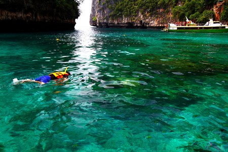 Asian man in orange life jacket with diving mask snorkeling with tourist boat and big mountain background on Andaman Sea, Krabi, Thailand with right copy space- Landmark in South of Thailand concept