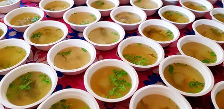 Many Hot green soup with sliced hatch and parsley or coriander leaves on top in white bowl for sale customer on table - Asian food with herb concept Stock Photo