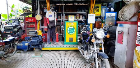 Ratchaburi, Thailand - September 26, 2018: Classic motorcycle parked with gas tank, clock, refrigerator and clothes show puppet at retro gasoline station or garage - Old stuff and Vintage collection