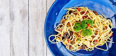 Flat lay or top view spaghetti with clams and mushroom sliced or Italian seafood pasta and parsley on top food in blue dish on gray wooden background or table with left copy space