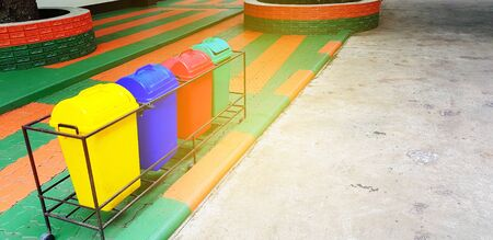 Colorful of four recycle bin or garbage for dumping waste on footpath with orange sunlight flare and copy space - Cleaning city, Green world and Reduce material concept Stock Photo