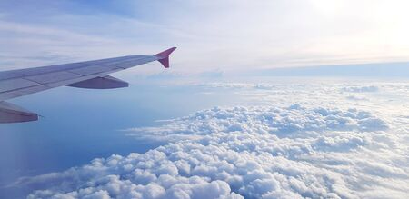 Aerial view of Aircraft or Airplane wing flying on sky and beautiful white clouds and copy space - Traveling, Soft of cloudy, Beauty of Nature at height est concept