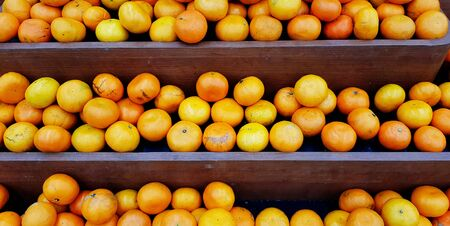 Fresh orange on brown wooden shelf for sale at organic fruit market or supermarket - Harvest, Diet food and Agriculture product concept