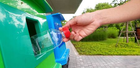 close up womans hand holding and dumping plastic bottle of water into green recycle bin, trashcan or trash with street and green garden background - Cleaning area and Recycling used concept 스톡 콘텐츠