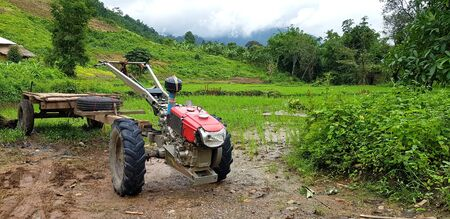 Red E-taen Thai tractor modifies to used for the shuttle and pick up or drop off people parked on mud ground with copy space and green mountain, trees and sky for background.