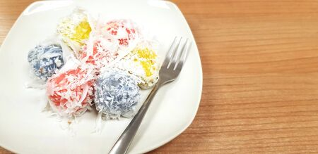 Close up Colorful Khanom Tom Daeng (Coconut Balls) with small fork in white dish or plate on brown wooden table with right copy space.