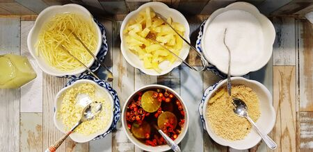 Flat lay or Top view group of ingredients with white sugar, sliced ginger, pineapple, fresh garlic, Ground beans, red Chili and fish sauce in white bowl for food at Thai restaurant.