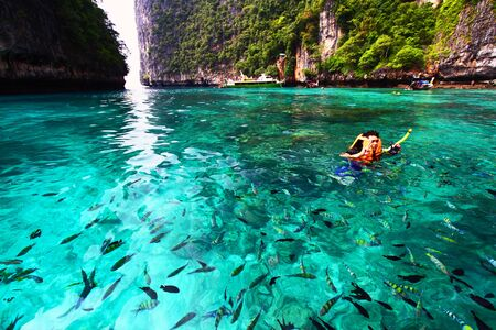 Krabi, Thailand - December 15, 2015: Asian man in orange life jacket with diving mask is snorkeling among many Indo-Pacific sergeant fish on Andaman Sea, Krabi, Thailand - Sport and Activity concept