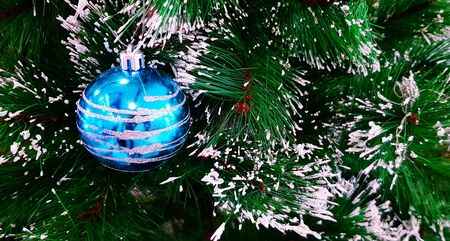 Blue ball with decorated on leaves of pine tree with snowflake and copy space. Happy new year, Christmas and Winter festival concept
