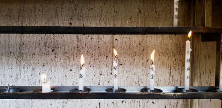 Japan - February 23, 2019: Light and Candles lit by people from faith, belief, fortune, blessing and exorcise on shelf at Japanese temples. Religion