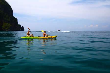 Krabi, Thailand-December 16, 2015: Two women in bikini or swimwear are enjoying canoe or kayak on Andaman Sea with speedboat, island and clear blue sky background and copy space. Asia travel, Activity Standard-Bild - 143145051