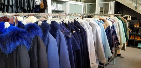 Many winter coats hanging on stainless steel hanger for rent or customer buy. Colorful sweater for sale at shopping store or market. Winter season cloth fashion. Фото со стока