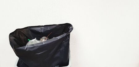 Black plastic bag containing full garbage isolated on white wall background with copy space on right. Keep cleaning and Take care environmental and Ecology concept