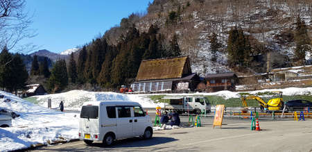 Japan - February 23, 2019: Small white van parked on street and people working and repairing or fixing damaged roads with snow on mountain and clear blue sky background Редакционное