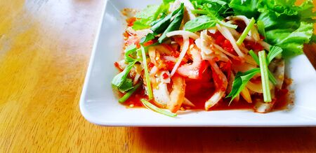 Close up spicy seafood salad with fresh tomato, onion, shrimp, shell and slices of celery in white dish or plate on wooden table. Asian or Thai food and Healthy eating style