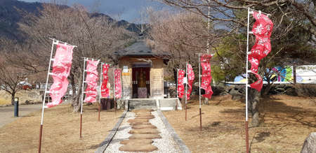 Japan - February 23, 2019: The walkway entrance to the shrine with many decorative flags and Autumn tree background. Religion and Belief or Faith.