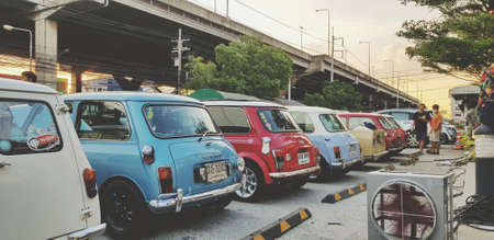Bangkok, Thailand - June 20, 2020: Many colorful mini Austin classic or cooper parked on street for group meeting with highway background. Vintage car or Retro style and Old vehicle concept