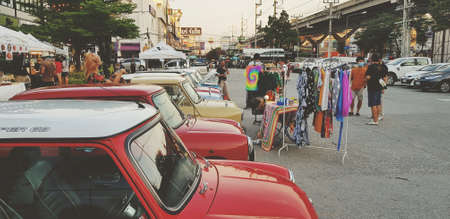 Bangkok, Thailand - June 20, 2020: Many classic mini Austin parking with dress shop on the local street market. Vintage cooper car or Retro vehicle with shopping landmark