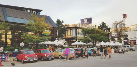 Bangkok, Thailand - June 20, 2020: Austin mini cars parked for sell stuff with colorful dress, vintage object and food at urban city of Bangkok. Classic, Group Vintage or Retro vehicle with city town.