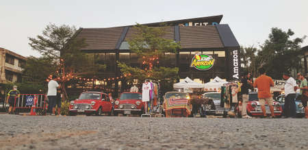 Bangkok, Thailand- June 20, 2020: Low perspective view of Classic mini cooper parked with people meeting at street market with coffee shop building background in vintage tone. Group of Austin car