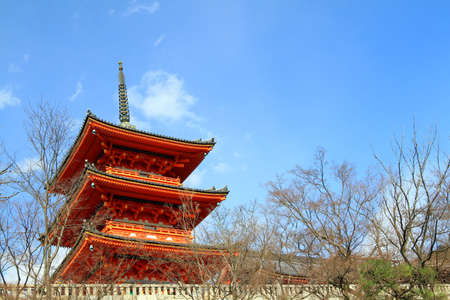 Red castle or Japanese temple with tree in fall and clear blue sky with copy space on right. This place call Itsukushima Shrine. Famous and landmark for travel or visit in Japan. Religion