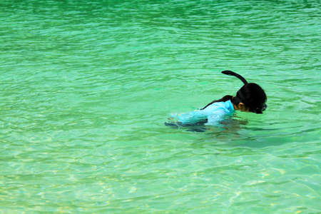Asian woman snorkeling or swimming alone in the Andaman Sea, Thailand with blank or copy space on left. Beauty in nature, Clear ocean, Sport, Activity and Landmark for Travel concept Фото со стока