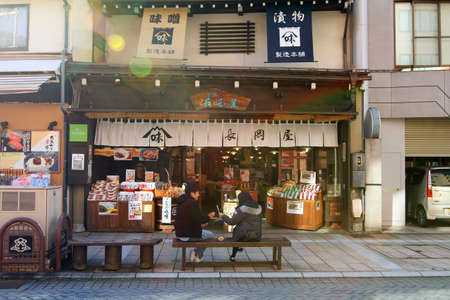 Japan - February 22, 2019: Young people, lovers, or friends eating food on the bench in front of the snack shop and souvenirs on street food at Takayama, Japan. Landmark for tourist travel and visit