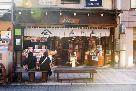 Japan- February 22, 2019: Two women or friends in coat sitting and talking bench in front of the snack shop and souvenirs after shopping on street food at Takayama, Japan. Landmark for visit or travel